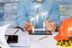Builder shows the ideas in the tablet . Builder shows the ideas in the tablet sitting at the table Stock Photo