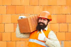 Builder shows thumb up. Labor protection at a construction site. Safety rules for builders. Happy builder in orange