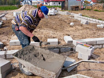 Builder on site. Builder holding mortar on a trowel whilst laying blocks on a building site Stock Photo