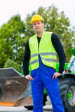 Builder on site in front of  construction machinery Stock Photo
