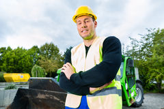 Builder on site in front of  construction machinery Royalty Free Stock Images