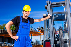 Builder with site pallet transporter or lift fork truck. Builder or driver with pallet transporter or lift fork truck on construction or building site Stock Photography