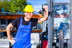 Builder with site pallet transporter or lift fork truck. Builder or driver with pallet transporter or lift fork truck on construction or building site Stock Photo