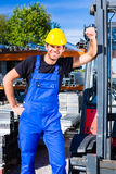 Builder with site pallet transporter or lift fork truck Stock Photography