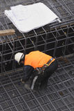 Builder and Site Plans. A builder secures steel mesh.  Various site plans rest nearby Royalty Free Stock Photos