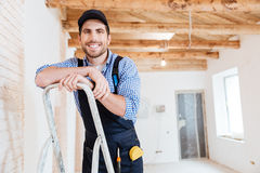 Builder smilling and holding pc tablet in his hands. Handsome builder smilling and holding pc tablet in his hands indoors Stock Photos