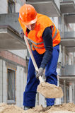 Builder spanning sand with spade Royalty Free Stock Photos