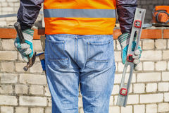 Builder with spirit level and hammer Stock Image