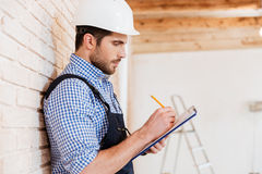 Builder standing backwards to the wall with clipboard Royalty Free Stock Photos