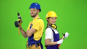 Builder standing a guy holding a drill, a girl hammer. Green screen. Builder stands a guy holding a drill, a girl with a hammer, they are preparing for a working stock video footage