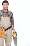 Builder standing with saw. Royalty Free Stock Photography