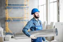 Builder with pipe indoors. Builder standing with ventilation pipe at the construction site indoors Royalty Free Stock Photos