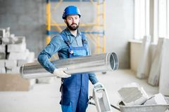 Builder with pipe indoors. Builder standing with ventilation pipe at the construction site indoors Royalty Free Stock Photography