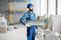 Builder with pipe indoors. Builder standing with ventilation pipe at the construction site indoors Royalty Free Stock Image