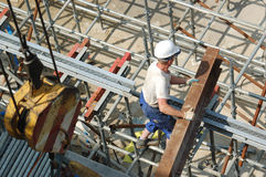 Builder with steel beam. Construction worker unloading steel beam on scaffolding Royalty Free Stock Photography