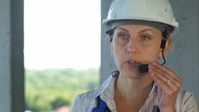 Builder supervisor oversees building site and gives instructions to workers over the intercom. Close up. Professional shot in 4K resolution. 104. You can use stock photography