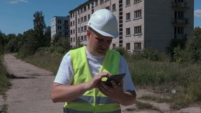 Builder take pictures near abandoned apartment houses stock video