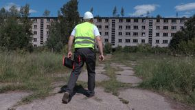 Builder take tool box near abandoned old apartment houses stock video