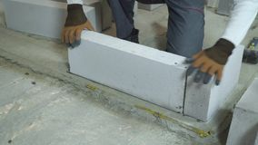 Builder taking aerated concrete block and laying it on cement foundation. Worker in uniform building interior wall at construction site. house renovation stock footage