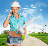 Builder talking on phone. Green hills, road, tower Stock Images