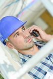 Builder talking on telephone. Adult Stock Photography