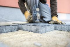 Builder tamping down a new paving slab or brick with motion blur. Builder tamping down a new paving brick with a mallet with motion blure effect Royalty Free Stock Photography
