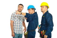 Builder team pointing away to a casual man. Builder man pointing and showing something to a casual man and his colleague over white background Royalty Free Stock Photos