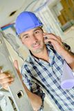 Builder on telephone holding stepladder. Adult Stock Photography