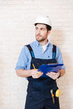 Builder thinking about something and holding a clipboard Stock Images