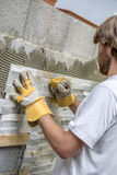 Builder tiling a wall Royalty Free Stock Image