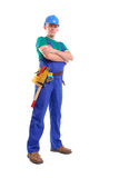 Builder with toolbelt. Builder wearing blue overall, toolbelt and hard hat posing over white background Stock Photos