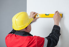 Builder turning back and holding a level and a pen Stock Photos