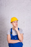 Builder in uniform and hard hat posing over white wall Royalty Free Stock Photo