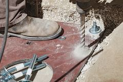 The builder uses a drill to make holes in a concrete. The builder uses an electric drill to make a hole in the concrete to further fix the metal plate Stock Image