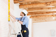 Builder using consruction level and standing n the ladder Stock Image