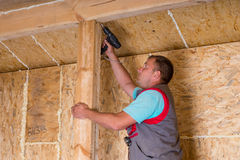 Builder Using Cordless Drill on House Frame Royalty Free Stock Images