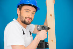 Builder using a drill looking at the camera Royalty Free Stock Photo