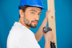 Builder using a drill looking at the camera Stock Photo