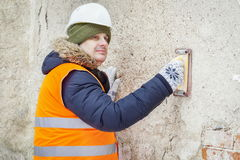 Builder using grinding tool and checking wall Stock Image