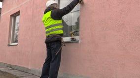 Builder using measure tape near window stock video