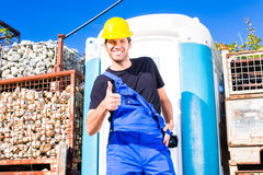 Builder using mobile toilet on site Stock Photo