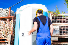Builder using mobile toilet on site Royalty Free Stock Photo
