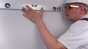 Builder using spirit level near wall in apartments. In room stock footage