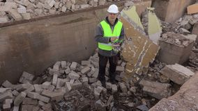 Builder using tablet PC on bricks ruins. In autumn day stock video