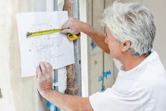 Builder using tape measure to check building plans Stock Photography