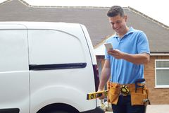 Builder With Van Checking Text Messages On Mobile Phone Outside stock photography