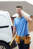 Builder With Van Talking On Mobile Phone Outside House Stock Photo