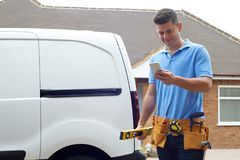 Builder With Van Texting On Mobile Phone Outside House Royalty Free Stock Images