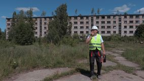 Builder with walkie talkie walking near abandoned apartment houses stock video