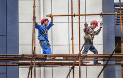 A builder walking on a scaffolding Stock Photo